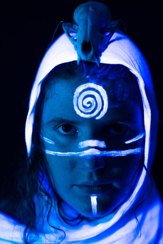 UV blacklight portrait of woman with a skull in a robe with a spiral pattern on her forehead looking forward in blue light
