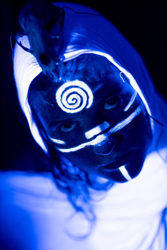 UV blacklight portrait of woman with a skull in a robe with a spiral pattern on her forehead looking up glowing