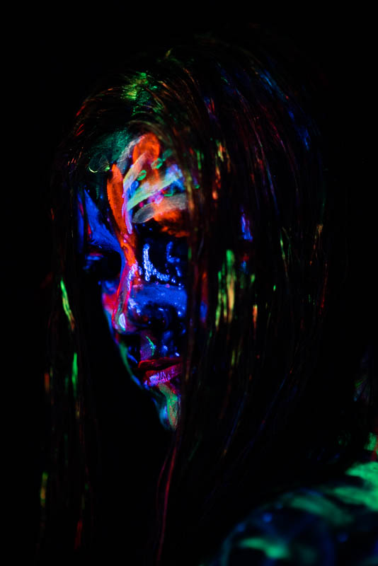 UV blacklight portrait of woman with face painted and hair in front of face