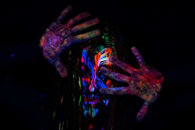 UV blacklight portrait of young woman with painted face and hands outstretched with messy hair
