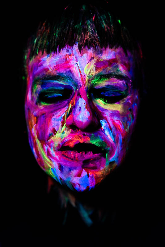 UV blacklight portrait of young woman with painted face and closed eyes looking forward
