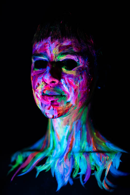 UV blacklight portrait of young woman with painted face with empty eyes and green neck