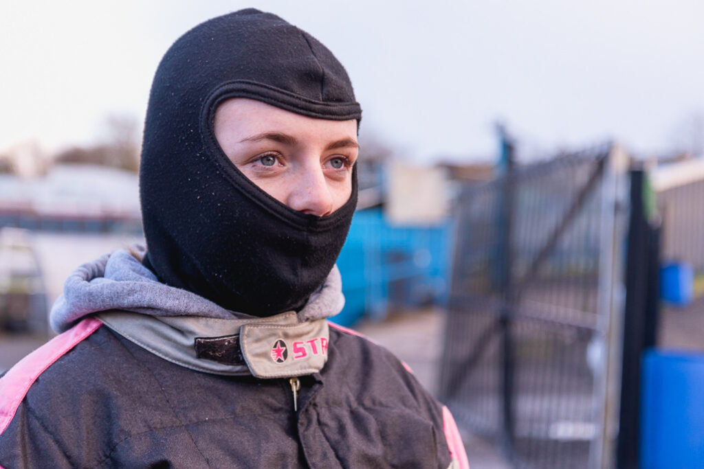 Taylor Borthwick Teenager Stock Car Racer portrait with protective helmet cover in front of racing tracks