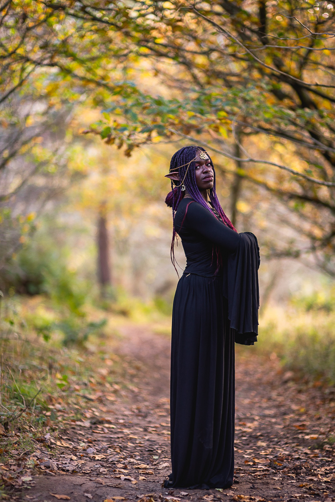 black fantasy elf woman standing in forest pathway among autumn leaves