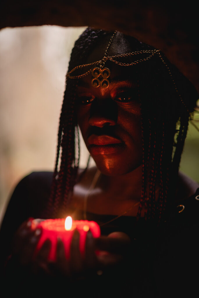 black fantasy elf woman looking down at candle in her palms in dark forest in Scotland