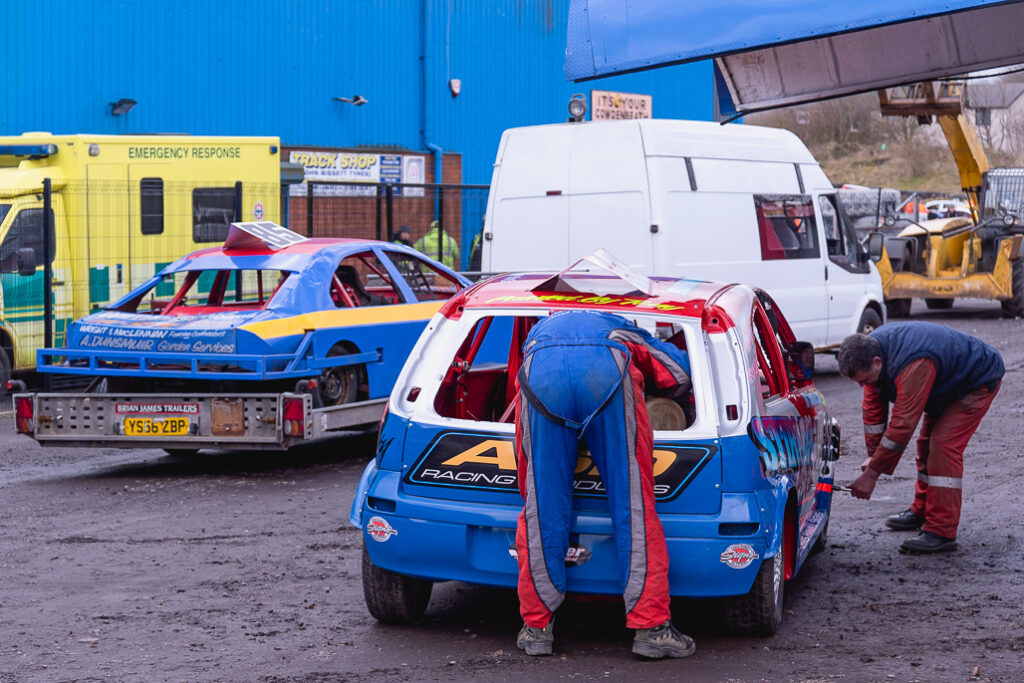 Men leaning over fixing up and preparing a stock car for racing