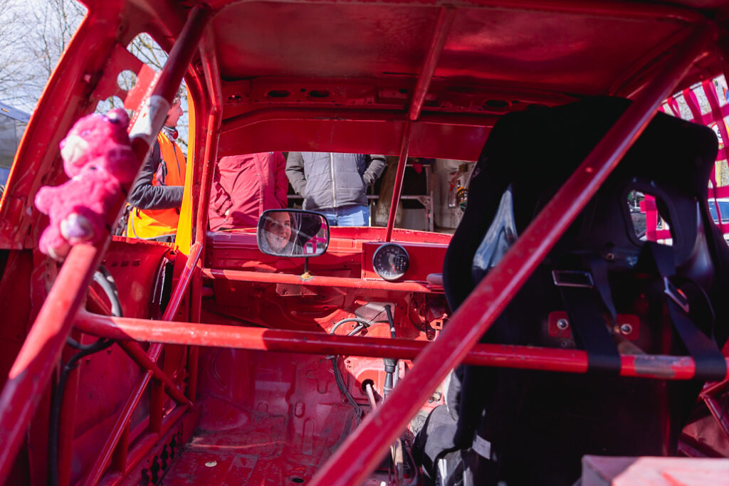 Taylor Borthwick Teenager Stock Car Racer in mirror of her racing car with plush toy in foreground