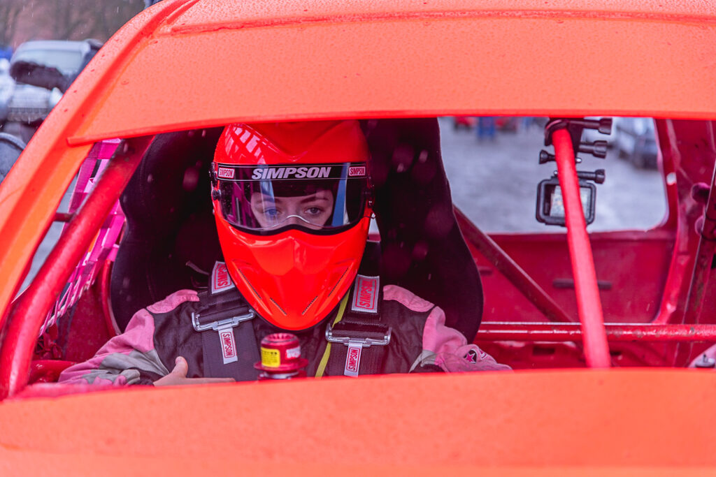 Taylor Borthwick Teenager Stock Car Racer in orange helmet and orange car before a race