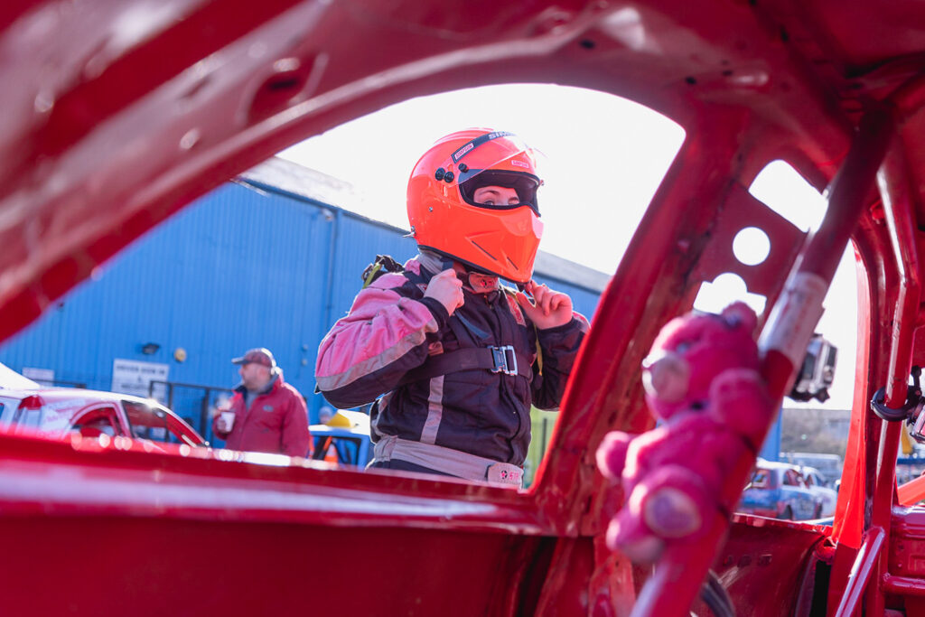 Taylor Borthwick Teenager Stock Car Racer putting on her bright orange helmet outside the car with a stuffed toy in foreground