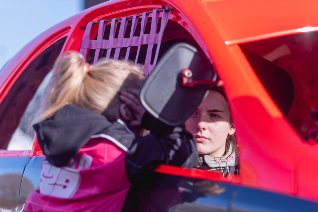 Taylor Borthwick Teenager Stock Car Racer, talking to her younger sister through the window