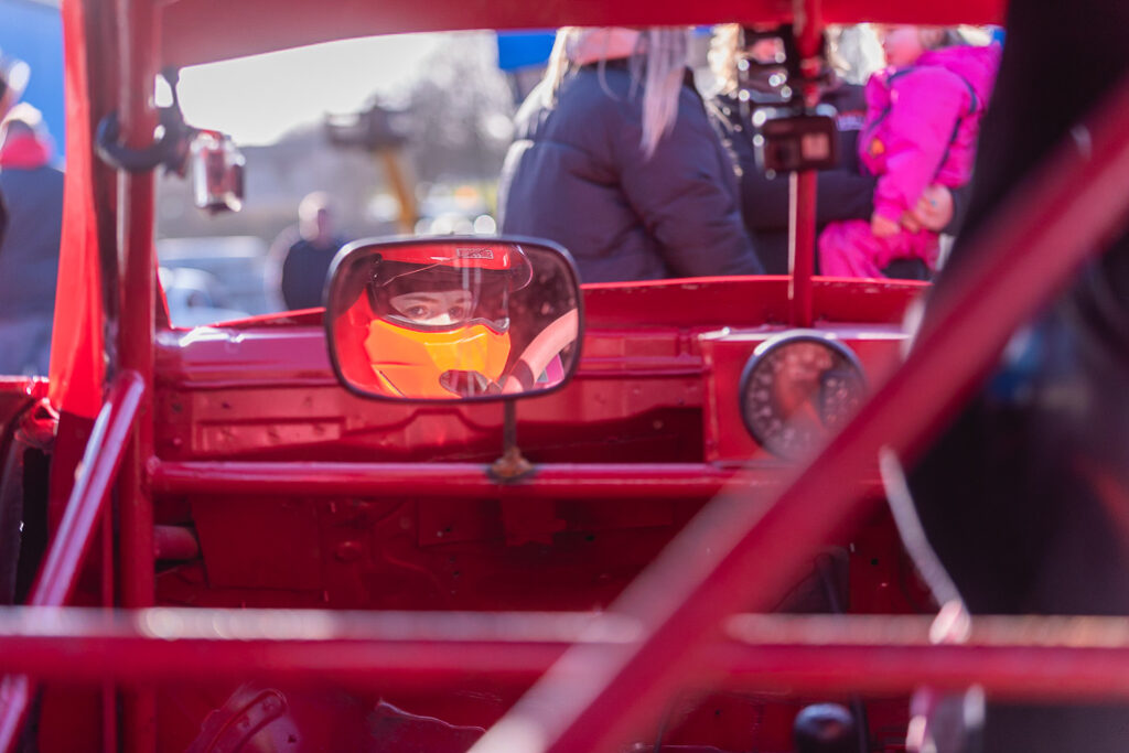 Taylor Borthwick Teenager Stock Car Racer in her card with helmet, reflected in the mirror