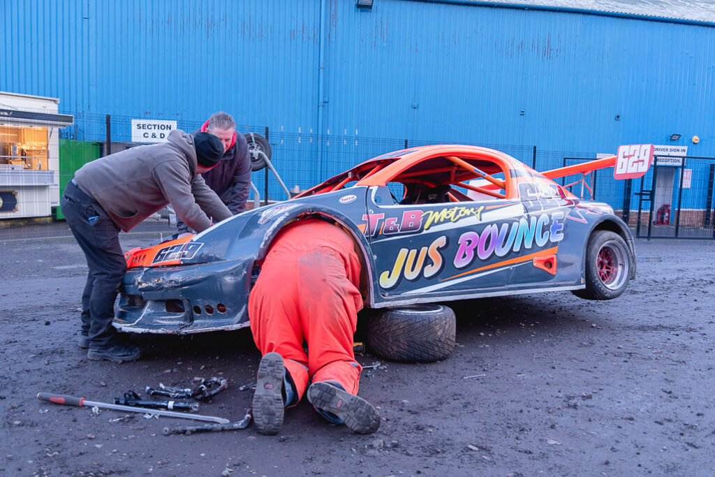 Stock car racers fixing up stock car before a race called Jus Bounce