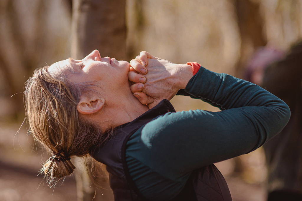 Woman Practicing Yoga as part of Adventure Yoga Edinburgh Class in forest stretching her neck muscles
