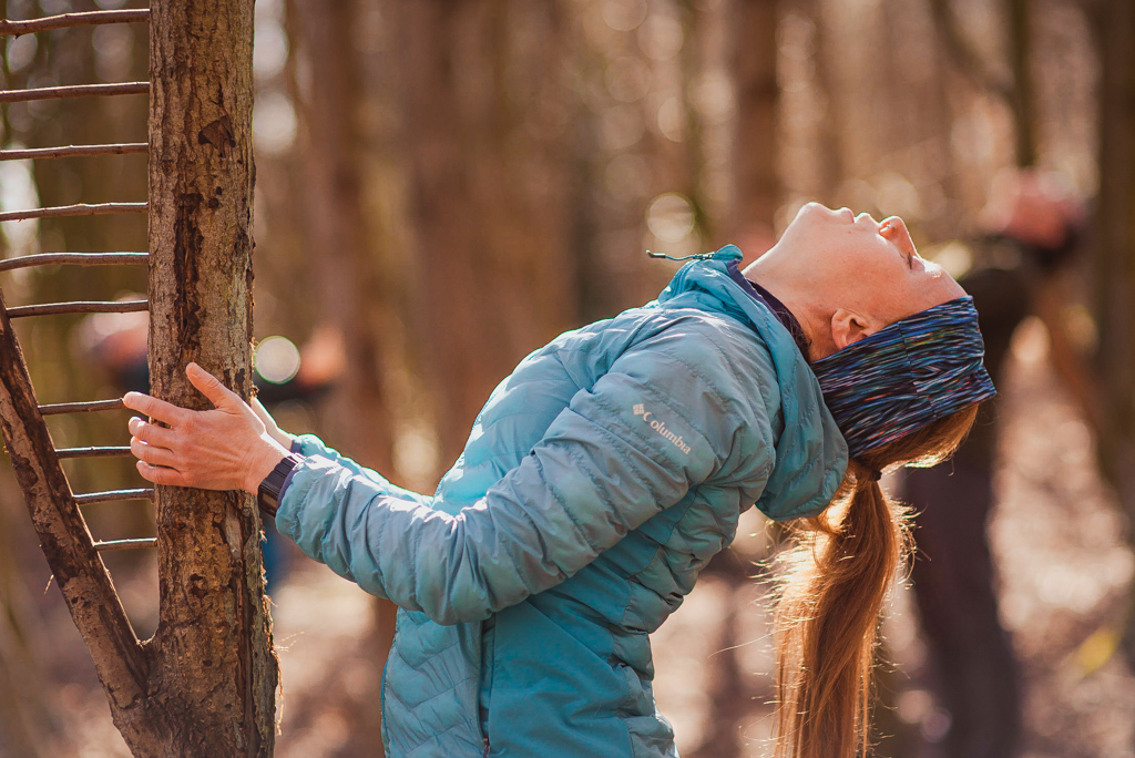 Woman performing backwards bend with tree support in a forest