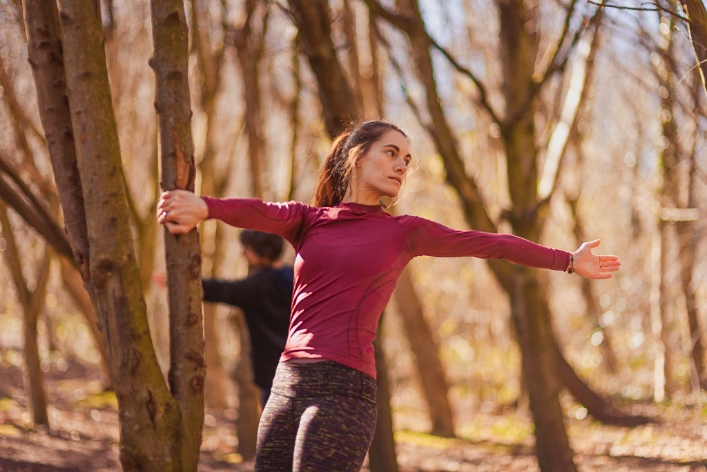 Stretching woman in forest as part of adventure yoga edinburgh yoga class in Holyrood Park