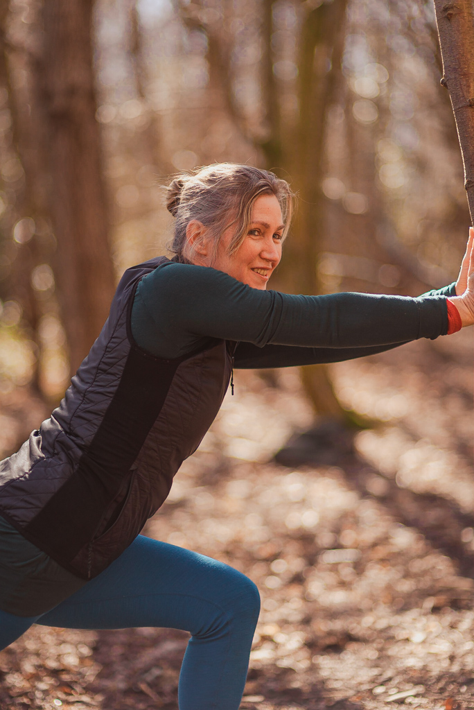 Woman stretching her legs in forest in Holyrood Park as part of yoga class