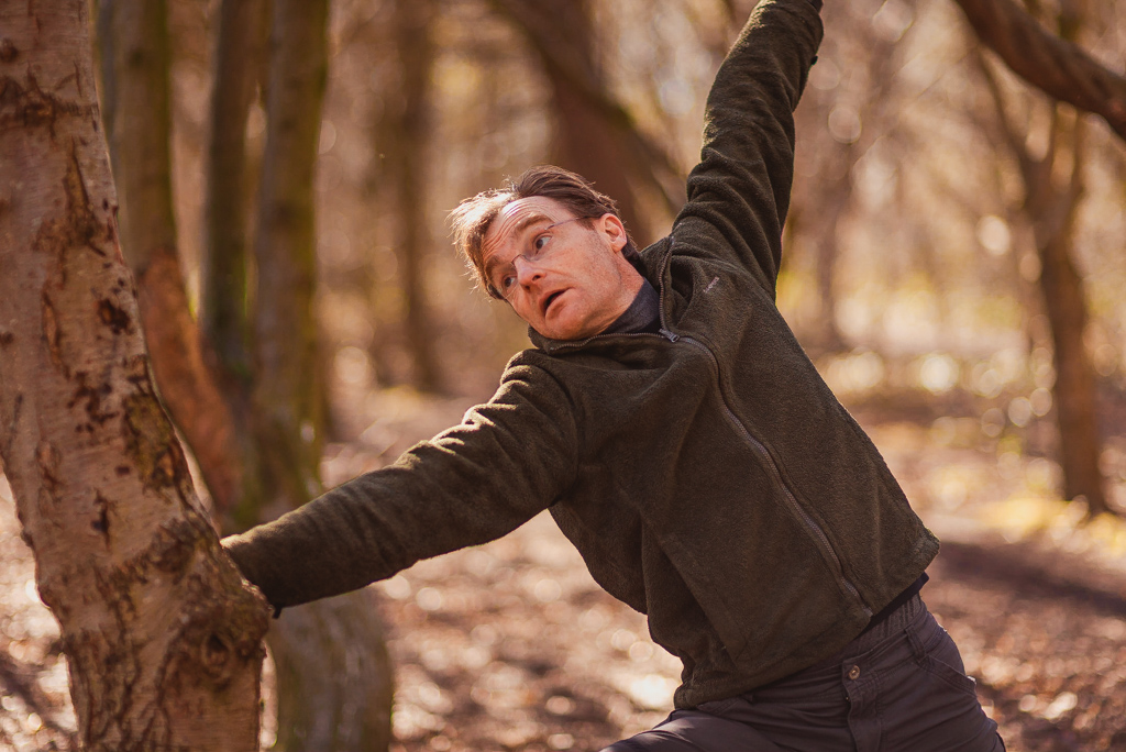Man stretching against tree in Holyrood Park as part of Yoga class