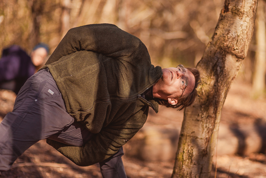 Man with glasses making under the legs hand bind in forest as part of a yoga class