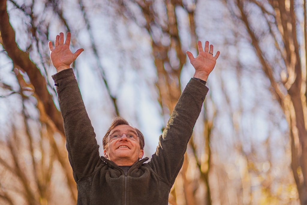 Happy man stretching up as high as possible in forest