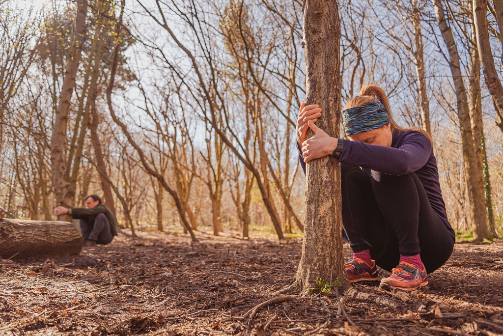 Woman pulling against tree while crouched to stretch
